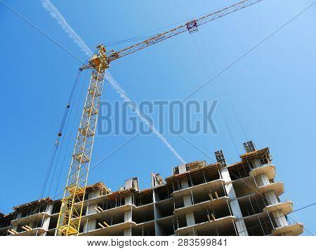 Construction Crane Near The Building Under Construction. Tower Crane On The Background Of Constructi