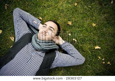 Young handsome man lying over green grass