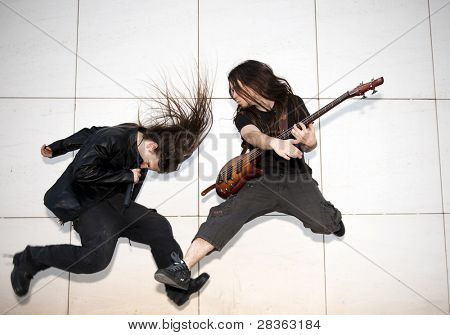 Two joung musician jumping against white wall