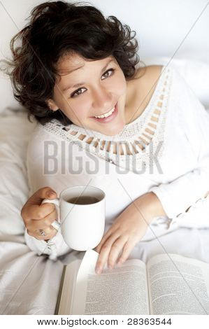 Woman reading and drinking tea on bed in sunday morning