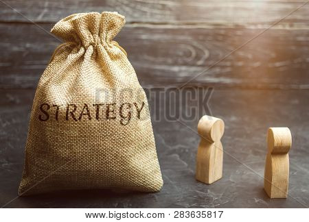 Two Businessmen Are Discussing Business Strategy. Business Strategy Is An Integrated Model Of Action