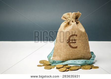 Money Bag With A Euro Sign And Tape Measure. Limited Budget. Lack Of Money. The Concept Of Accumulat