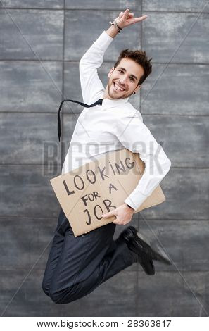 Young man jumping with a Looking for a job sign