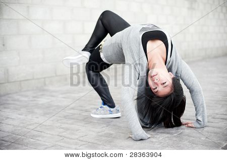 Asian girl doing bridge pose in gym clothes.