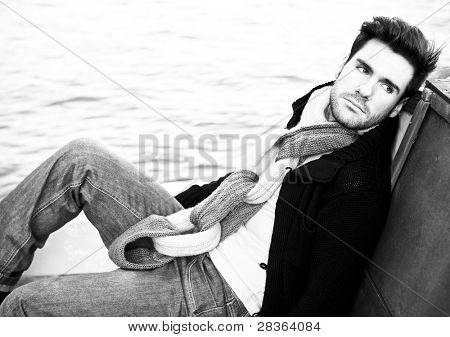 Portrait of a handsome young lying on wooden texture.