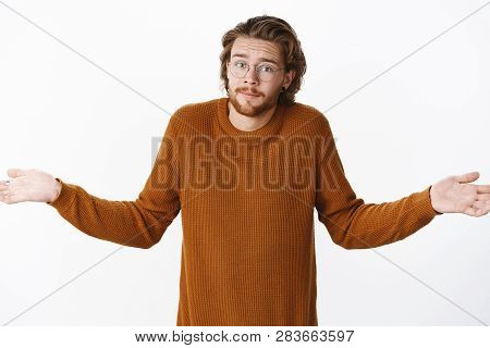 Waist-up Shot Of Clueless Unaware Young Bearded Man In Glasses With Wavy Hairstyle Raising Hands Sid