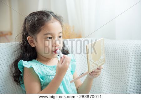 Cute Asian Daughter Sitting On Sofa And Putting Lipstick On Her Lips At Home.