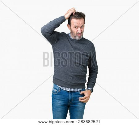 Handsome middle age senior man wearing a sweater over isolated background confuse and wonder about question. Uncertain with doubt, thinking with hand on head. Pensive concept.