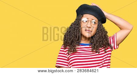 Young beautiful woman with curly hair wearing glasses and fashion beret confuse and wonder about question. Uncertain with doubt, thinking with hand on head. Pensive concept.