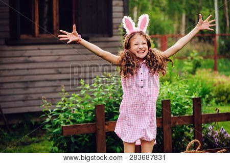 Easter Portrait Of Happy Child Girl In Funny Bunny Ears Playing Egg Hunt Outdoor At Wooden Country H