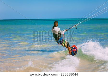 Egypt, Hurghada - 30 November, 2017: Close-up rear view of the surfer on the surfboard holding the kite straps. The wave riding over the crystal clear Red sea surface. Overwhelming marine landscape.