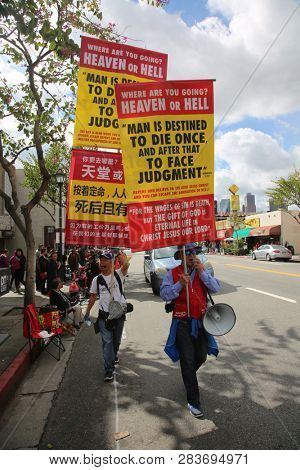 LOS ANGELES - FEBRUARY 9, 2019: Golden Dragon Parade in the streets of China Town Los Angeles. People hold Judgment Day Signs and Chant during the Chinese New Year celebration 2019.
