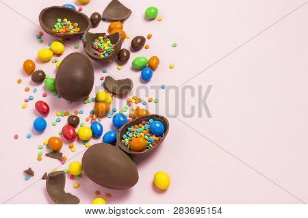 Broken And Whole Chocolate Easter Eggs, Multicolored Sweets , Pink Background. Shrub. Concept Of Cel