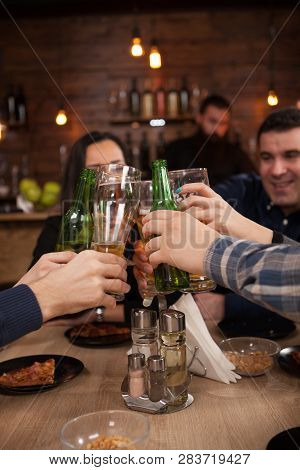 Group Of Happy Friends Drinking And Toasting Beer At Brewery Bar Restaurant.