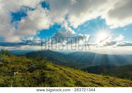 Summer Mountain Scenery At Sunset. Stones On The Grassy Meadow. Distant Ridge Beneath A Cloudy Sky.