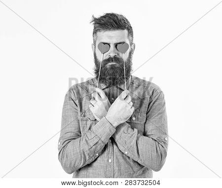 Brutal Man In Love. Blind From Love. Hipster With Paper Red Hearts And Serious Face. Bearded Man Hol