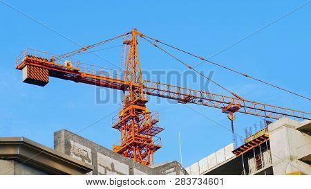 Crane. Construction Crane. Huge Crane And Concrete Building Against Blue Sky. Self-erection Crane. T