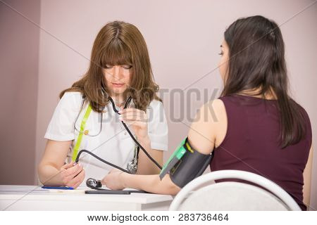 Cosmetology Beauty Clinic. Doctor Checking Patients Blood Pressure And Looking At The Pressure Gauge