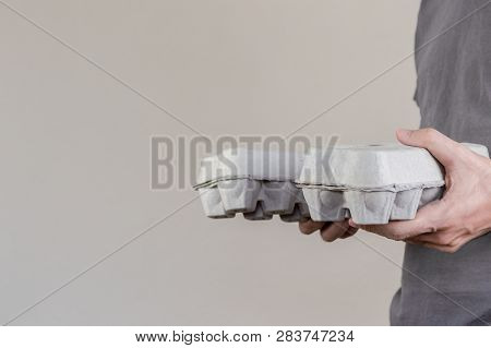 Caucasian Man With Gray T-shirt Holding Two Cardboard Egg Boxes Full Of Hen Eggs.