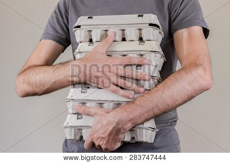 Caucasian Man With Gray T-shirt Holding Four Cardboard Egg Boxes Full Of Hen Eggs