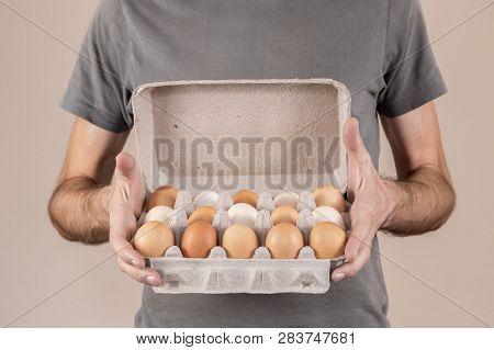 Caucasian Man With Gray Tshirt Holding A Cardboard Egg Box Full Of Hen Eggs.
