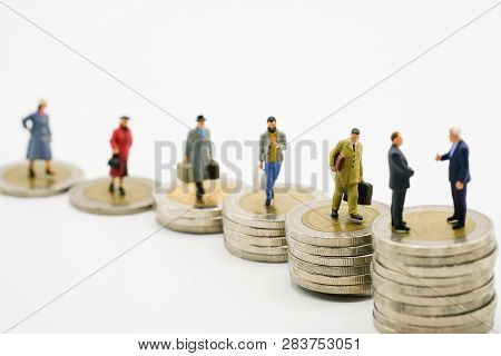 Miniature Business Man Model On Increase Of Stacking Coins Money With White Background. Income And E