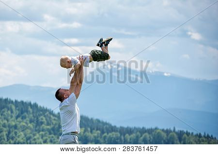 Happy Father Throws Up A Little Son Against A Background Of Green Forest, Mountains And Sky With Clo
