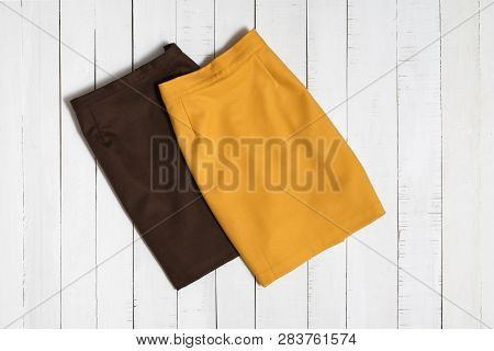 Fashion Clothes. Brown And Orange Mini Skirts On White Wooden Floor Planks