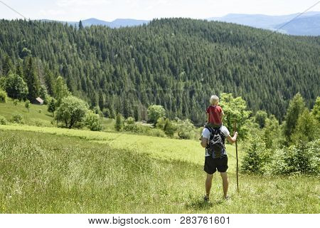 Father With Son On His Shoulders Standing With Staff In The Background Of Green Forest, Mountains An