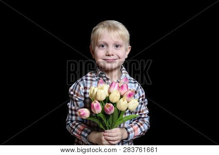 Small Smiling Blond Boy Holding A Bouquet Of Tulips. Portrait. Isolate On Black Background