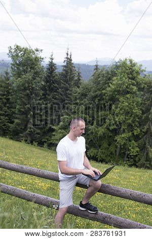 Man Sits On A Wooden Fence And Works With A Laptop Near The Field And Coniferous Forest. Vertical Fr