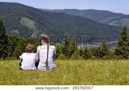 Mother And Young Son Sitting On Grass On The Background Of Coniferous Forest And Mountains.