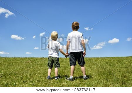 Two Little Brothers Stand Holding Hands On A Green Field Against A Blue Sky And Clouds. Brotherhood
