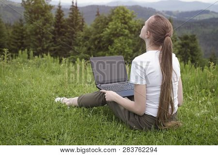 Beautiful Dreaming Girl With A Laptop Sitting On Green Grass On A Background Of Mountains.