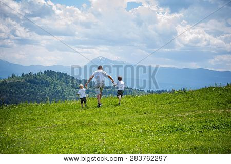 Father And Two Young Sons Running On The Green Field Holding Hands On Background Of Green Forest, Mo