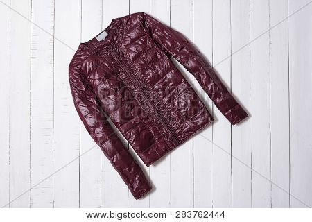 Fashion Clothes. Burgundy Short Jacket On White Wooden Floor Planks