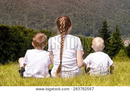 Mother And Two Young Sons Sitting On Grass On The Background Of Coniferous Forest And Mountains.