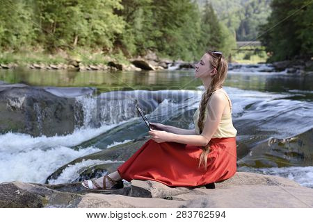 Pensive Beautiful Long-haired Girl In A Red Skirt Sits With A Laptop On A Stone Against The Backdrop