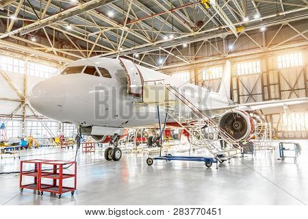 Aviation Hangar With Passenger Aircraft Jet For Maintenance.