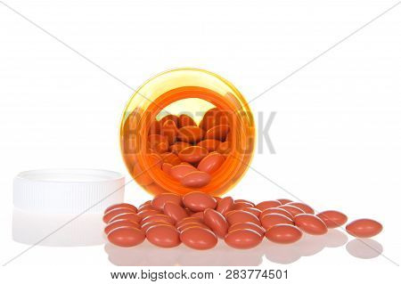 Medication Bottle On Side With Pills Spilling Out Onto A Reflective Surface, Lid Beside. Reflection