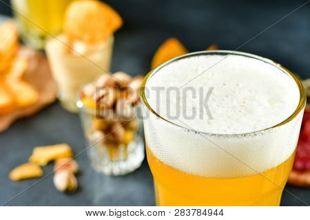 Two Glasses Of Beer And Snacks Chips, Nachos With Sauce, Pistachios And Salami, Aperitif, Relax In T