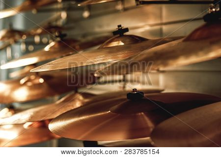 Choosing Drum Set. Close Up View Of Several Golden Drum Cymbals In A Music Shop. Music Concept