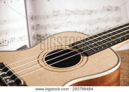 Ukulele Chords. Close-up Photo Of Ukulele Guitar And Music Notes Against Of Wooden Background. Music