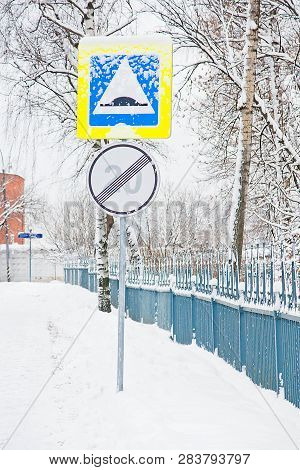 Road Signs Under The Snow Near The Fence