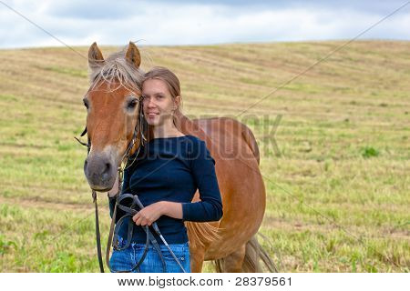 Young girl with her horse in meadow