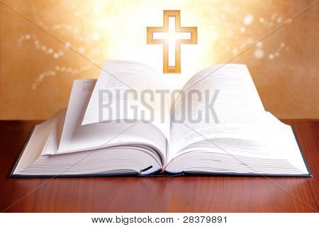 Open holy bible with peaceful light and cross