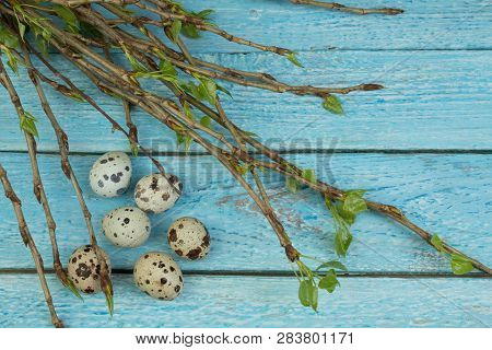 Easter Eggs And Branch With Leaves On Wooden Table Background. Top View. Copy Space For Text.