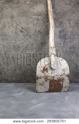 Old, Dirty Shovel On The Gray Concrete Background. Copy Space. Top View.