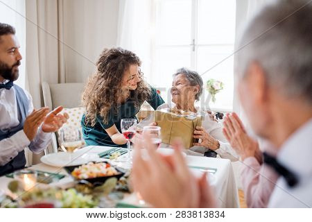 An Elderly Grandmother Celebrating Birthday With Family And Recieving A Gift, Party Concept.