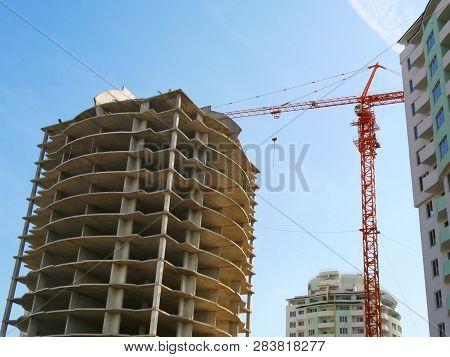 Concrete Building Under Construction Against The Blue Sky. Construction Site.